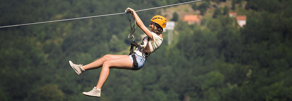 Girl Using a zip wire over a forist